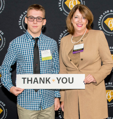Student holds Thank You sign with Foundation Board member