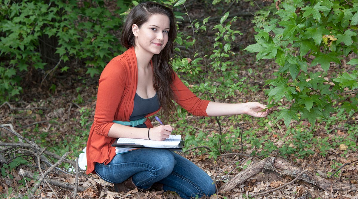 Student takes notes while examining a leaf in the woods