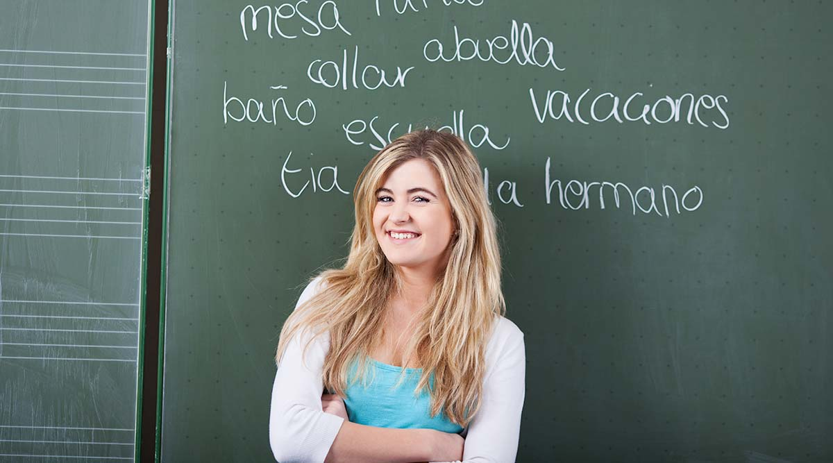 Student stands in front of a blackboard with Spanish words written on it