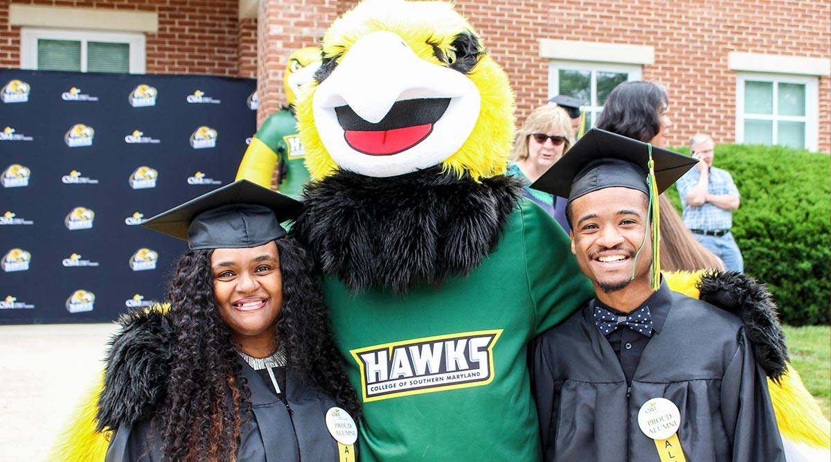 Graduates pose in their caps and gowns with Hawk mascot